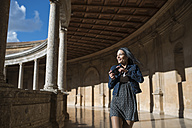 Spain, Granada, happy young woman with camera at the Alhambra - JAS01672