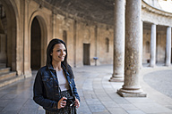 Spain, Granada, smiling young woman with camera at the Alhambra - JAS01675