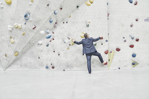 Back view of businessman standing in front of climbing wall in a bouldering hall - FMKF03873