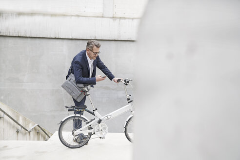 Businessman with folding bicycle looking at cell phone - FMKF03885