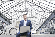 Businessman sitting on wall using laptop - FMKF03888