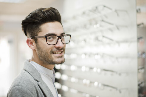 young man trying on glasses at the optician's - JASF01680