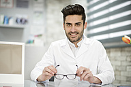 Optician holding glasses in his shop - JASF01692