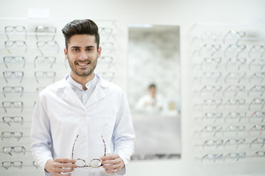 Optician holding glasses in his shop - JASF01695