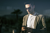Young man holding smartphone, reading messages - JASF01704