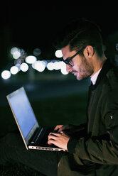 Young man using laptop at night - JASF01722