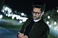 Young man using smartphone at night - JASF01725