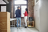 Businesswoman talking to young colleague in office - RHF01864