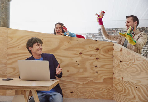 Young businessman working on laptop with colleagues playing hand puppets behind wooden wall - RHF01873
