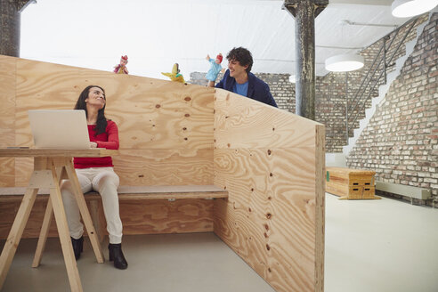 Businesswoman working on laptop with colleagues playing hand puppets behind wooden wall - RHF01876