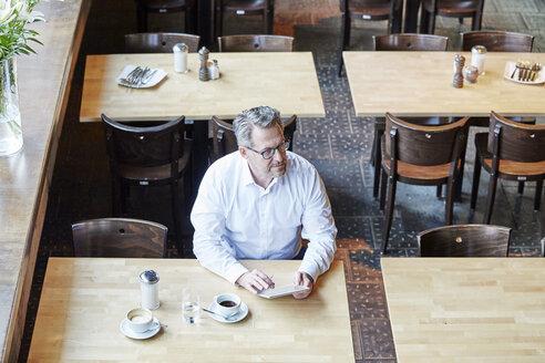 Mature businessman in cafe using tablet - FMKF03915
