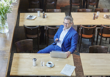 Mature businessman in cafe with laptop, cell phone and earbuds - FMKF03918