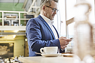 Mature businessman in cafe using cell phone - FMKF03930