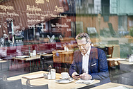 Mature businessman in cafe using cell phone - FMKF03936