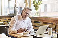 Mature businessman in cafe using laptop and cell phone - FMKF03942