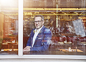 Confident mature businessman looking out of window - FMKF03945