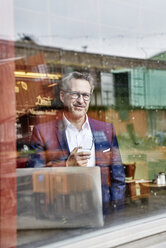 Confident mature businessman with laptop looking out of window - FMKF03948