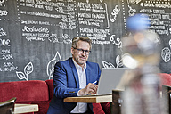 Portrait of confident mature businessman in cafe using laptop - FMKF03951