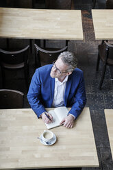 Mature businessman in cafe writing in diary - FMKF03957
