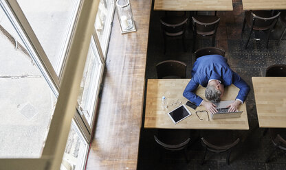 Exhausted mature businessman in cafe with laptop, tablet and cell phone - FMKF03960
