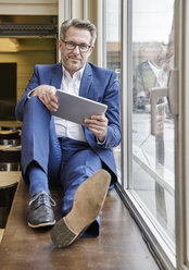 Relaxed mature businessman using tablet at the window - FMKF03963