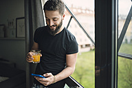 Young man drinking an orange juice and using his smartphone at the window - RAEF01832