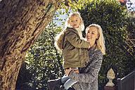 Happy mother carrying daughter in garden - KDF00719