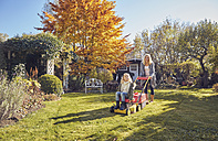Mother with daughter in garden lawnmowing - KDF00722
