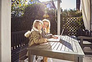 Mother with daughter at garden table using laptop - KDF00728