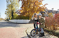 Mother talking to daughter with bicycle - KDF00731