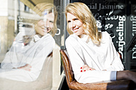 Smiling businesswoman in a cafe looking out of window - FMOF00181