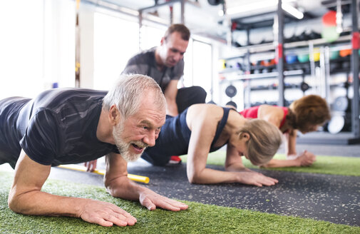 Group of fit seniors with personal trainer in gym - HAPF01454