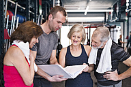 Group of fit seniors and personal trainer in gym looking in folder - HAPF01466