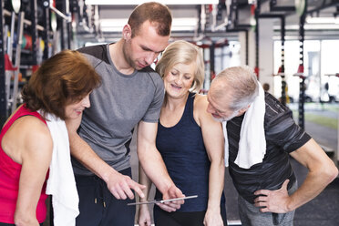 Group of fit seniors and personal trainer in gym looking at tablet - HAPF01469