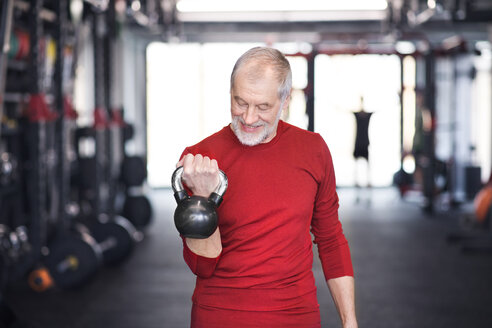 Senior man exercising with kettlebell in gym - HAPF01481
