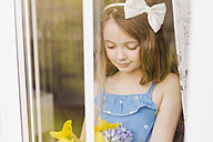 Portrait of smiling girl with cut flowers behind windowpane - NMSF00044