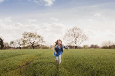 Smiling girl running on a field - NMSF00047