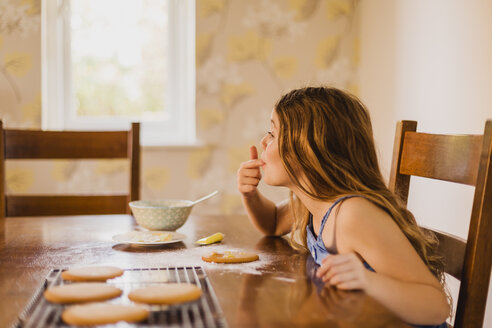 Girl decorating biscuits at home - NMSF00053