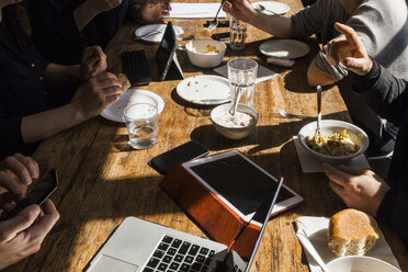Colleagues having lunch together in the office, partial view - TCF05368