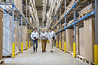 Three men walking in factory warehouse - DIGF01720