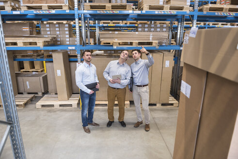 Three men with tablet talking in factory warehouse - DIGF01723