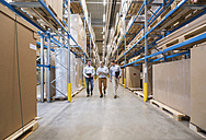 Three men walking in factory warehouse - DIGF01726