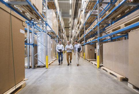 Three men walking in factory warehouse - DIGF01726
