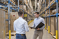 Two men with folder talking in factory warehouse - DIGF01732