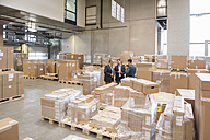 Three men in factory warehouse surrounded by cardboard boxes - DIGF01741