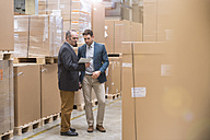 Two men looking at tablet in factory warehouse - DIGF01753