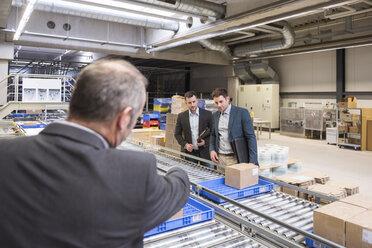 Three businessmen at conveyor belt in factory - DIGF01759