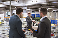 Three businessmen at conveyor belt in factory - DIGF01762