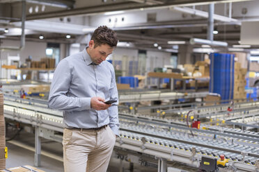Man at conveyor belt in factory looking at cell phone - DIGF01765