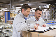 Two men in factory warehouse looking at documents - DIGF01774